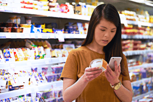 Insights. A consumer looking at a label in a supermarket and checking the ingredients on her phone.