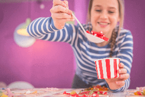 Confectionery. A girl pouring sweets into a tub.